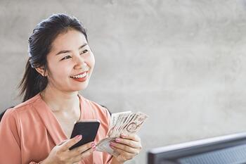 happy-asian-woman-hand-holding-smart-phone-banknotes_34670-767