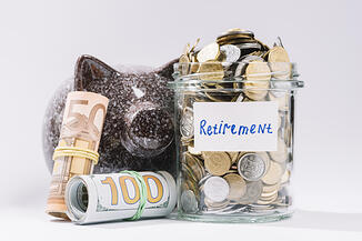 rolled-up-banknotes-piggybank-retirement-container-full-coins-white-backdrop_23-2147919312