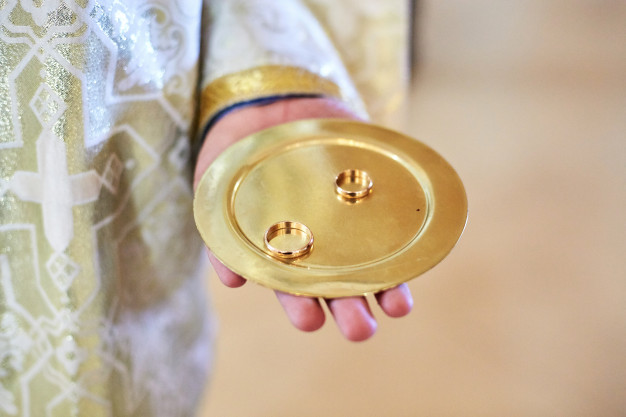 priest-holds-plate-with-golden-wedding-rings_8353-1744